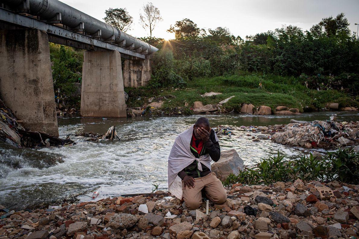 Listen Dube (37) se arrodilla para rezar a orillas del río Jukskei, municipio de Alexandria, en ...