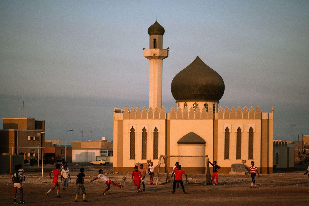 Niños juegan al fútbol frente a una mezquita recientemente construida en Madinat 'Isa, Baréin, en 1979.