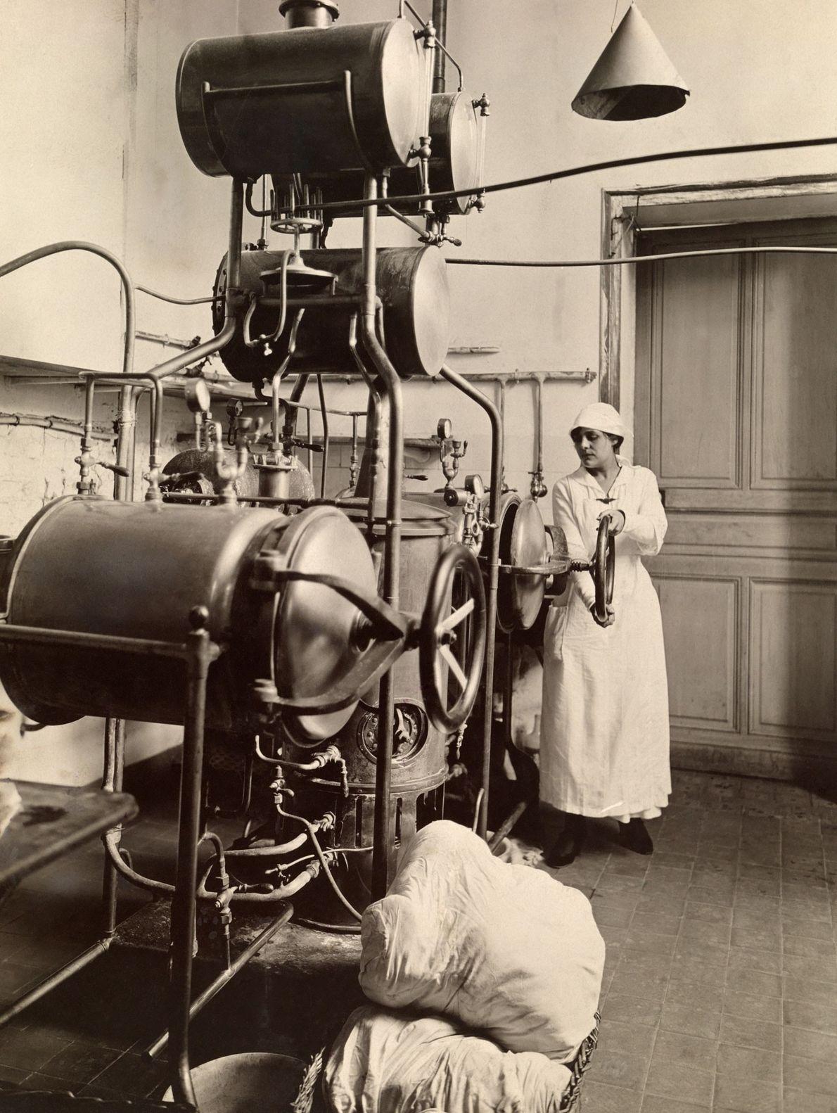 Una mujer trabaja en la cámara de esterilización durante la Primera Guerra Mundial en un hospital ...