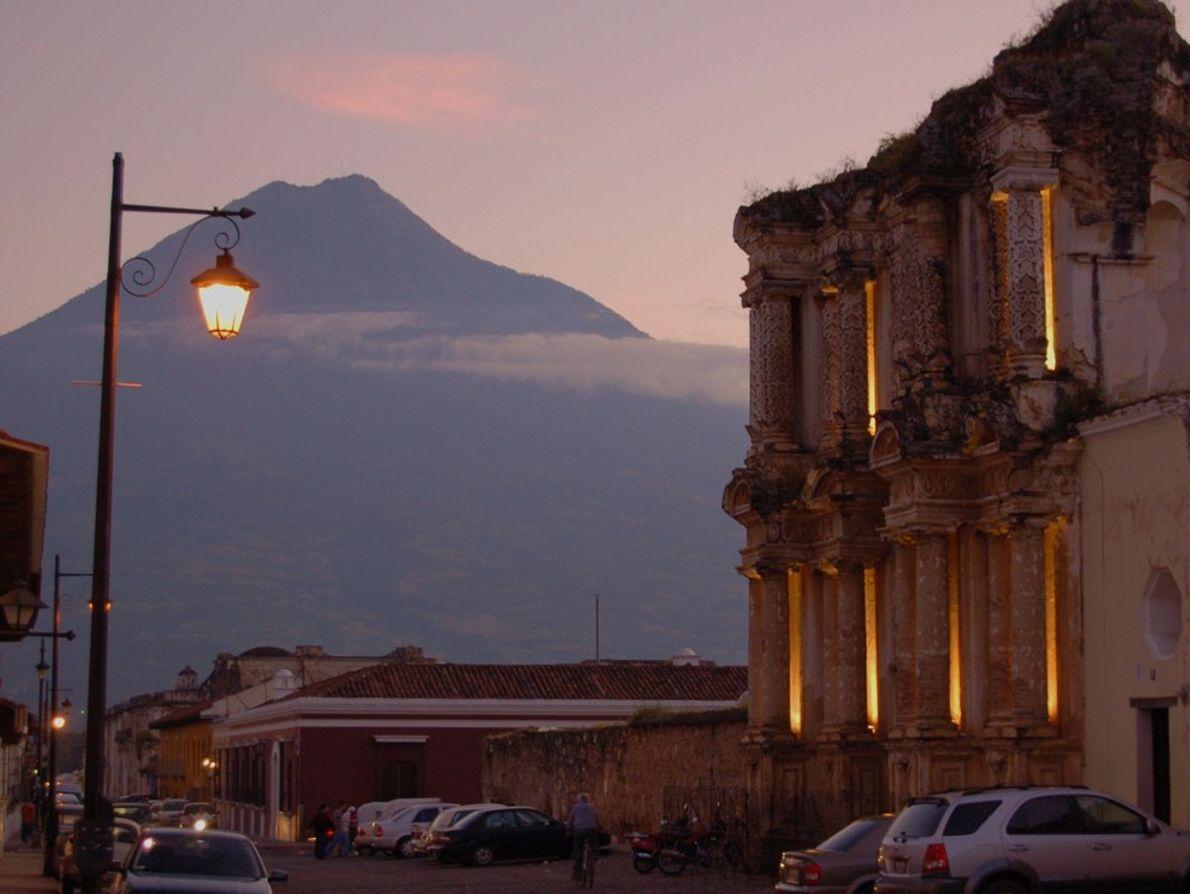 Una iglesia desmoronada en la ciudad de Antigua Guatemala, y como telón de fondo, un volcán ...