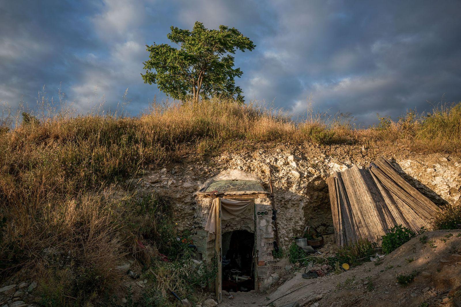 La puerta de entrada de una cueva sobresale ligeramente de una pared rocosa en Sacromonte. Muchas ...