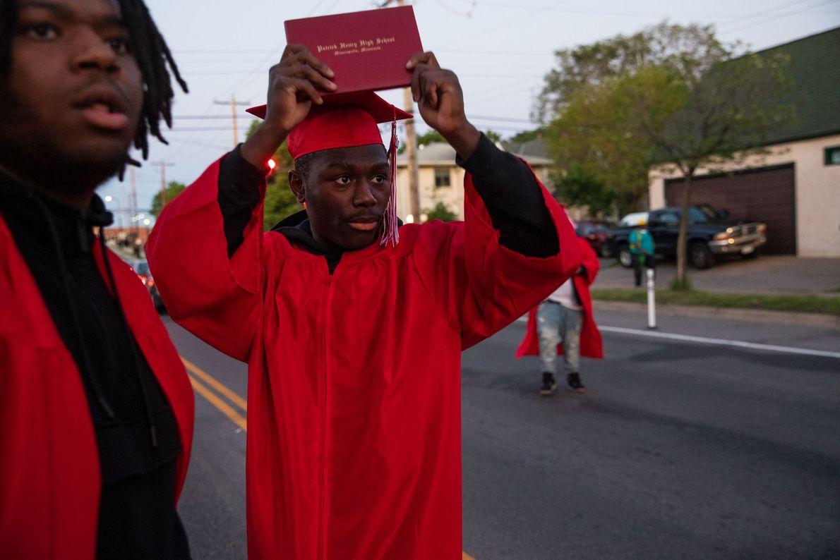 Datelle Straub levanta su diploma mientras la policía se acerca a los manifestantes. Él y sus ...