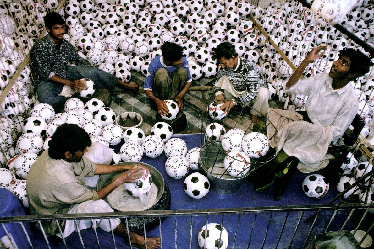 Jóvenes trabajadores lavan las pelotas en una fábrica de pelotas de fútbol en Sialkot, Pakistán, en ...