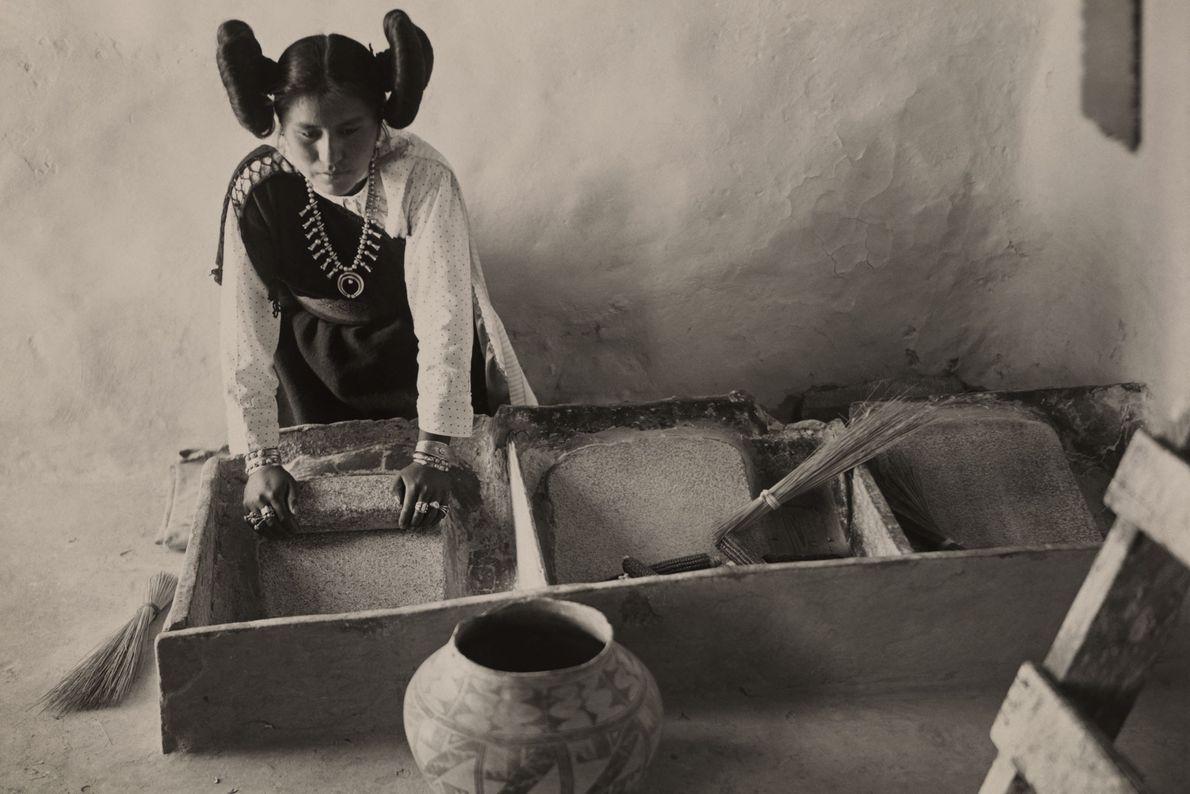 En Walpi, Arizona, una mujer hopi se arrodilla mientras trabajaba con sus manos en 1921.