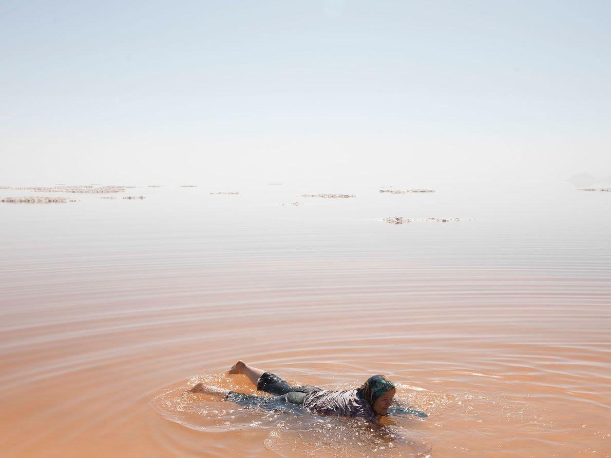 Una niña salpica agua en el lago Urmia, Irán. Los bañistas de verano se adentran en ...