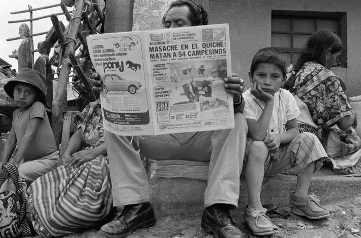 Un hombre lee sobre la masacre de 54 personas en la región de Quiché en 1982. ...