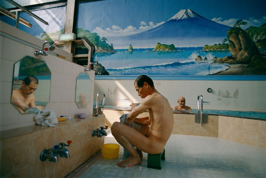 Un hombre se baña en una casa de baños de Tokio decorada con un mural del ...