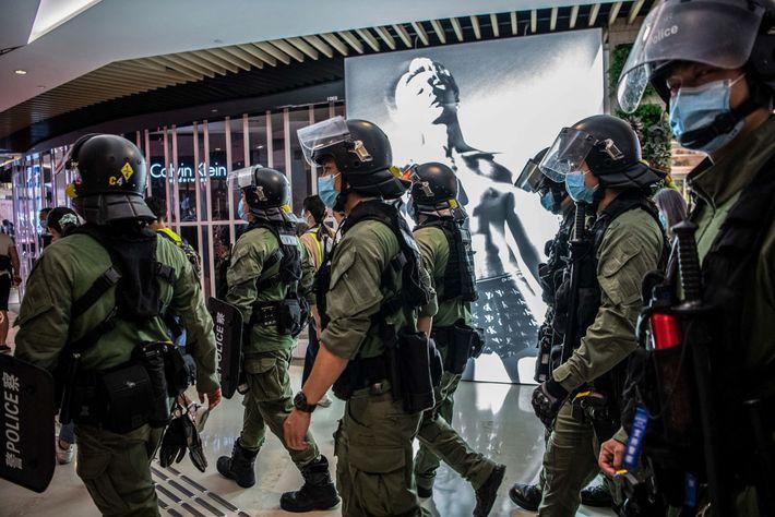 La policía camina por el centro comercial YoHo Mall en Yuen Long, Hong Kong, el 21 ...