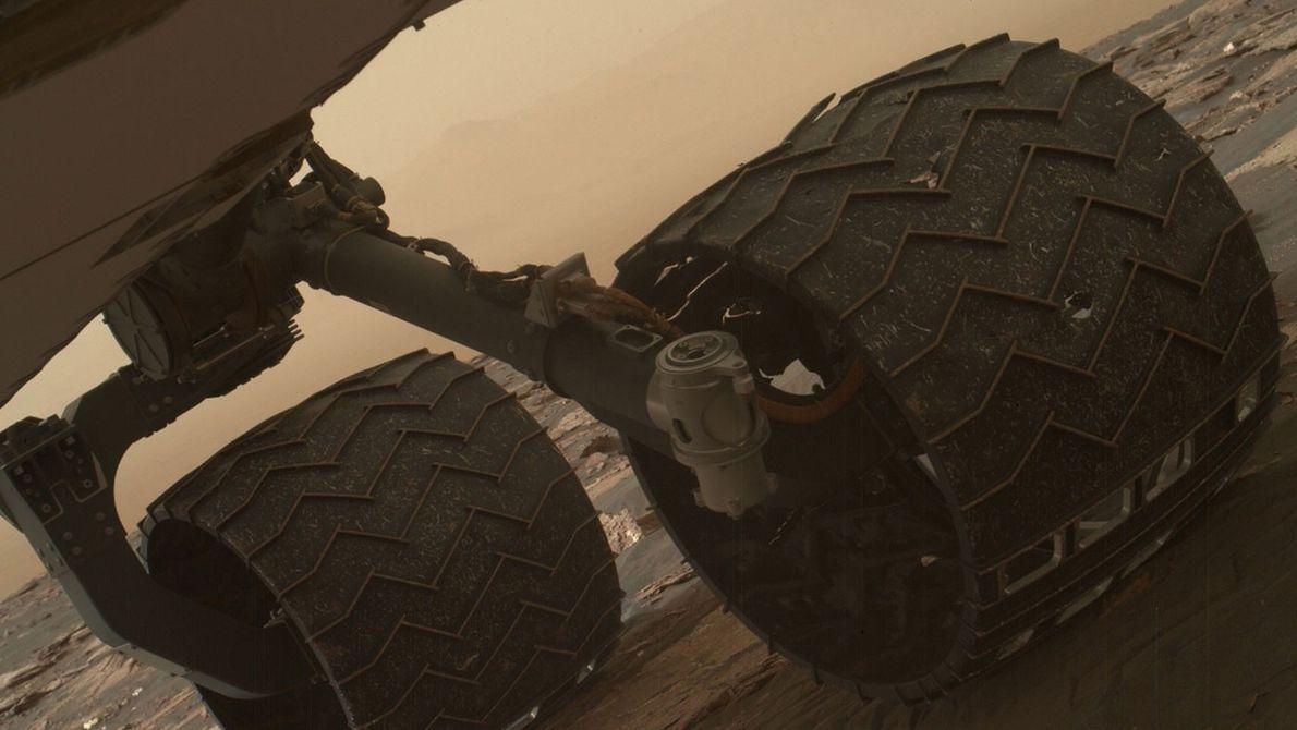 Dos de los relieves de la rueda media izquierda del rover Curiosity de la NASA se ...