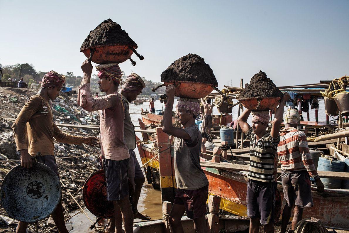 Trabajadores migrantes bangladesíes descargan arena de barcos de propiedad india en Thane Creek, India.