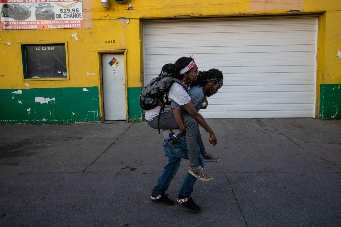 Un hombre lleva a un amigo herido por las balas de goma de la policía durante las ...