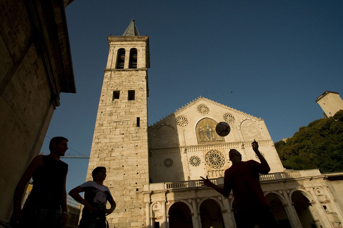 Un pequeño grupo juega al fútbol frente a la Catedral Santa Maria Assunta en Umbría, Italia.
