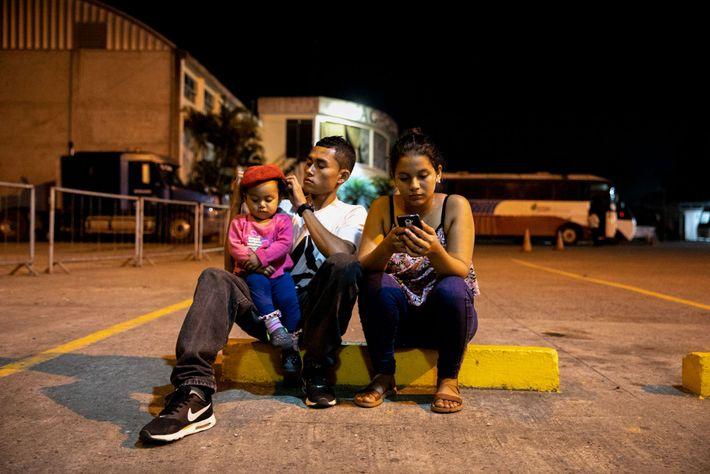 Moisés Cubas y Meya Chávez abrigan a su hija, Gimena, en una parada de autobús en ...