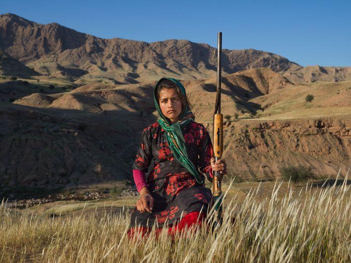 En Irán, una adolescente sostiene la escopeta de su madre.