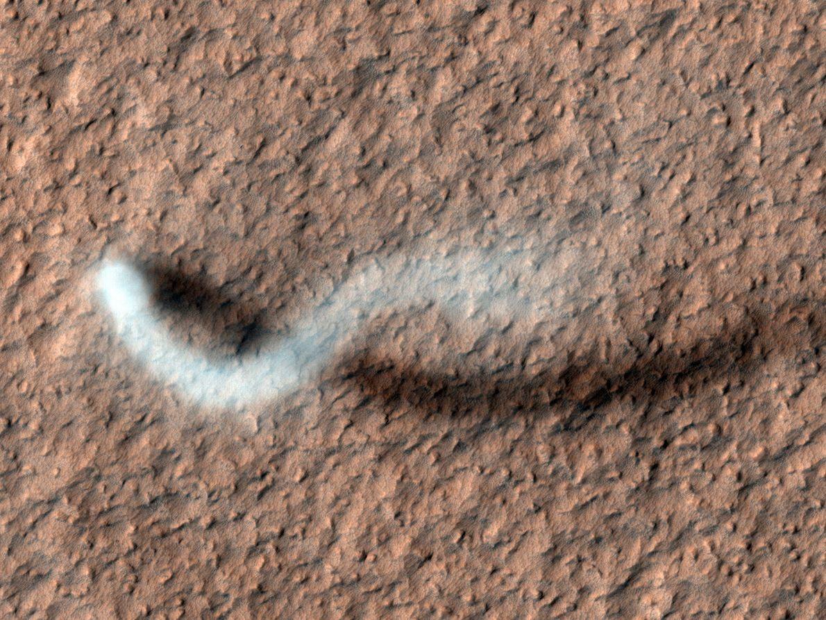 Un diablo de polvo proyecta una sombra serpentina sobre la superficie de Marte en esta impresionante ...