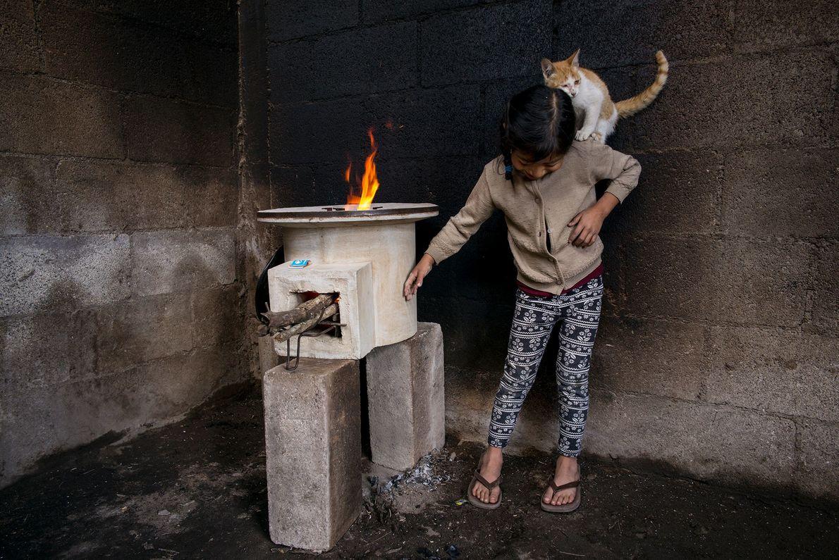 Tania López, de siete años, juega con su gato en una habitación de su casa en ...