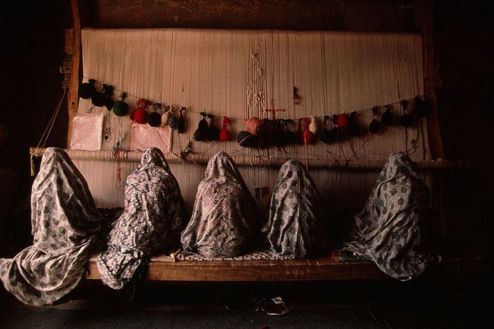 Una familia de mujeres iraníes trabaja  en un telar tejiendo alfombras para la exportación.