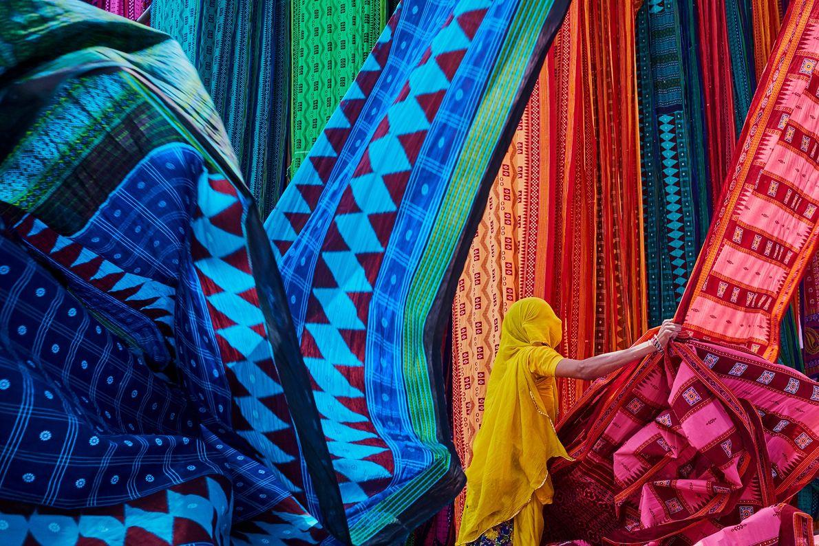 En la fábrica Saree en Rajasthan, los trabajadores cuelgan los textiles recién teñidos al sol para ...