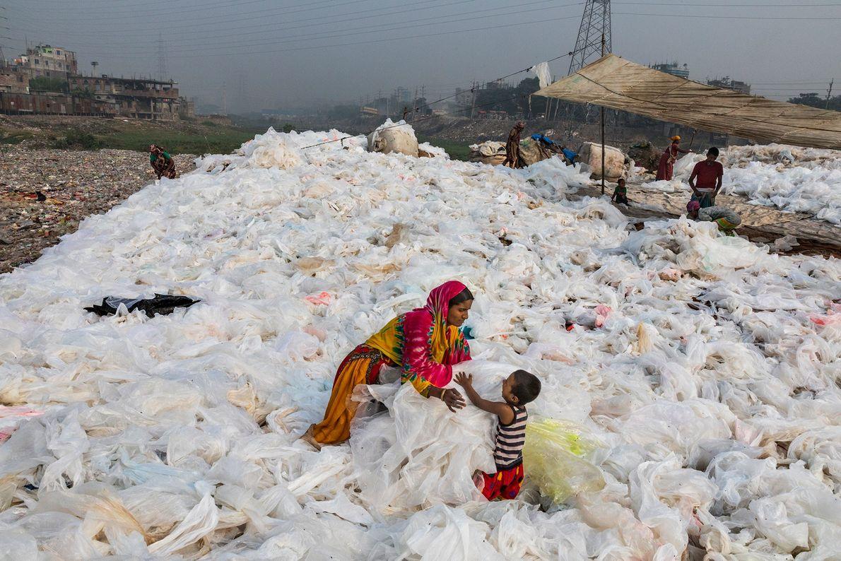 Después de lavar láminas de basura de plástico transparente en el río Buriganga, una mujer las ...