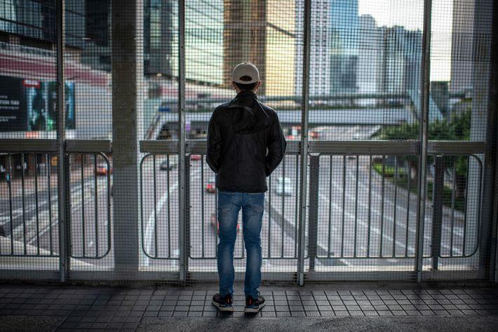 Un manifestante de 19 años en una pasarela peatonal con vista a Harcourt Road, el sitio ...