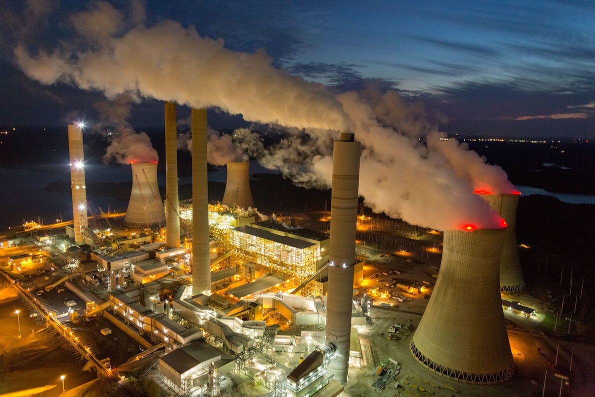 El vapor y el humo se elevan desde las torres de enfriamiento y las chimeneas de ...