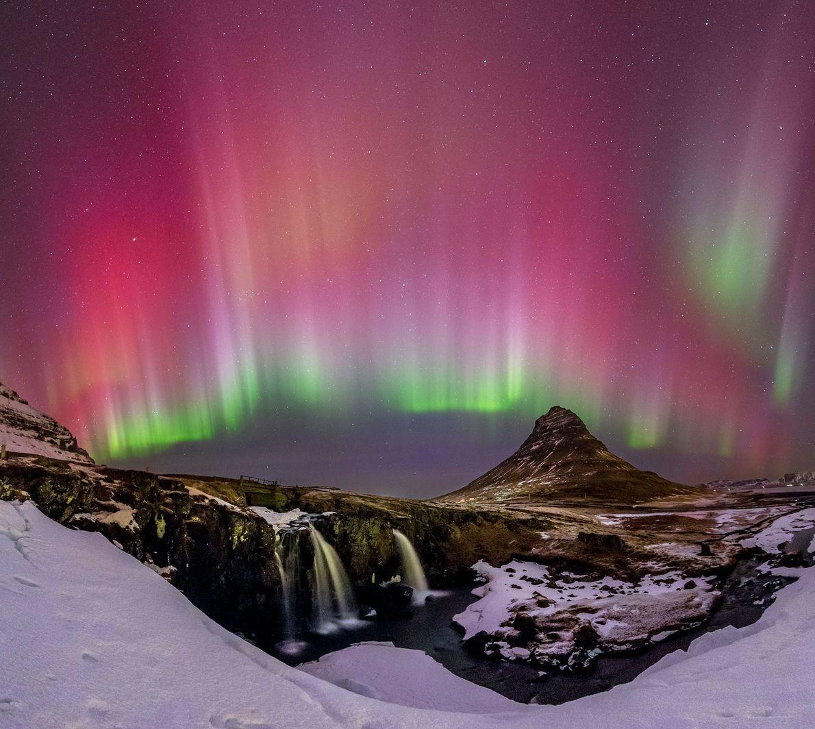 Una vista nocturna de una cascada en Islandia, resaltada por la aurora boreal.
