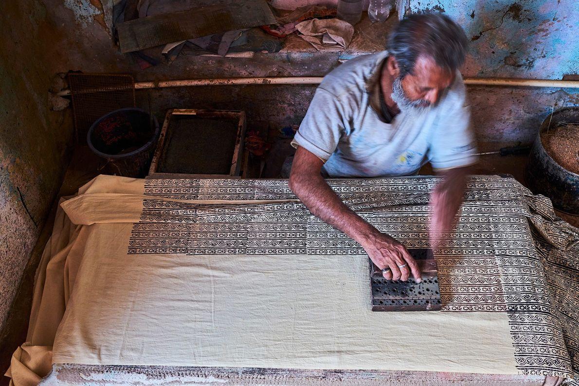 Un artesano utiliza un bloque de madera para imprimir la tela sari en Rajasthan, India. La ...