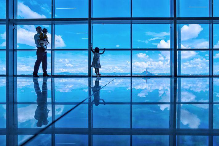 Mirando hacia el azul salvaje, un padre y sus hijos parecen caminar sobre las nubes en ...