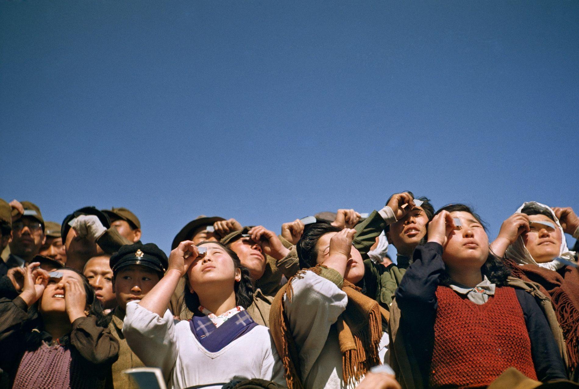 Varias personas observan un eclipse solar a través de láminas o cristales ahumados en la isla Rebun en Japón.