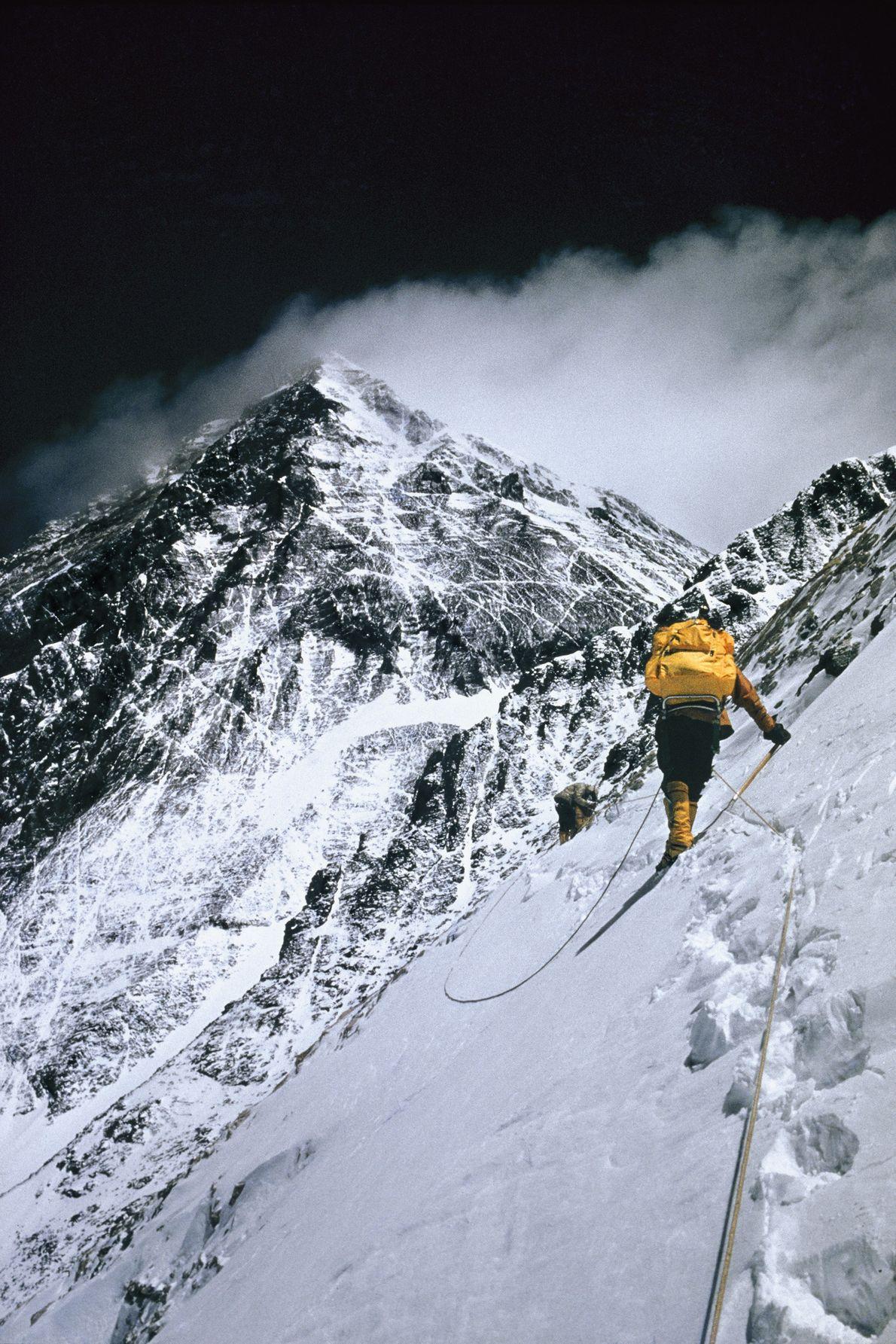 Los escaladores cruzan la vertiginosa pendiente del Lhotse a 25,000 pies (alrededor 7620 metros). Acompañado por ...