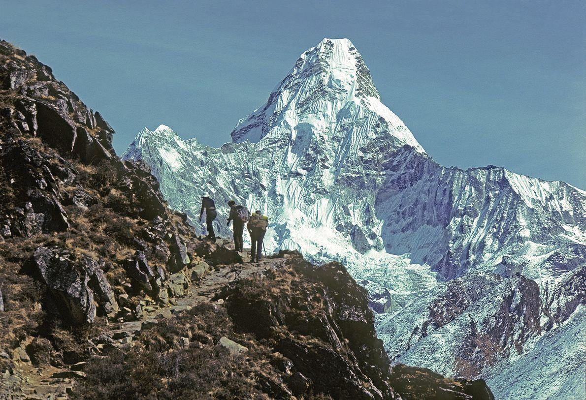 Los excursionistas en la ruta principal hacia el Monte Everest en 1979 pasan por Ama Dablam, ...