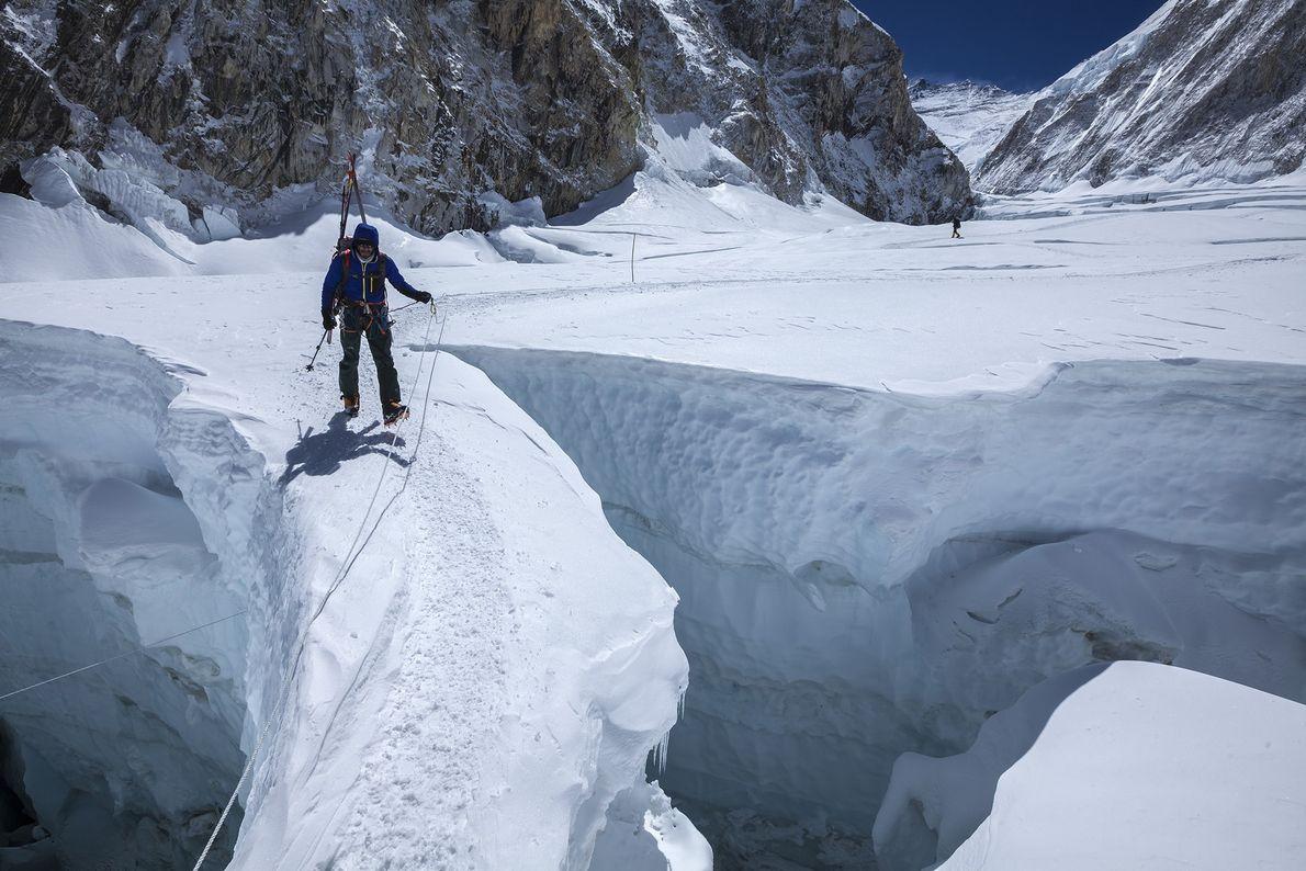 Un escalador cruza un estrecho puente de hielo en el Khumbu Icefall en 2012. A menudo ...