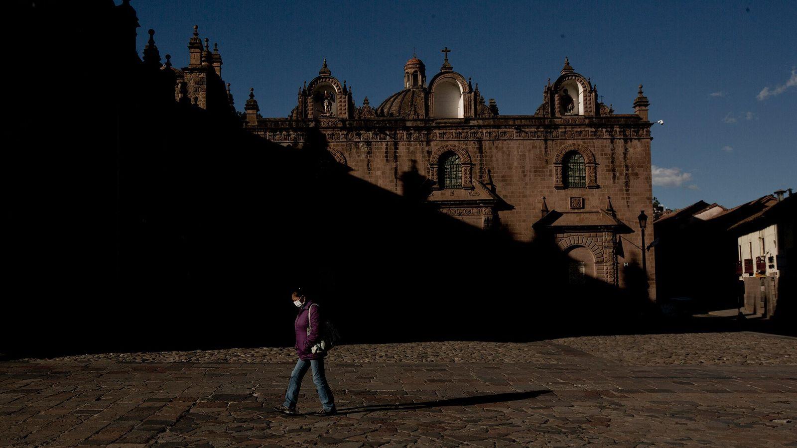 En el otoño de 2020, una mujer camina por la Catedral de Cusco en lo alto ...