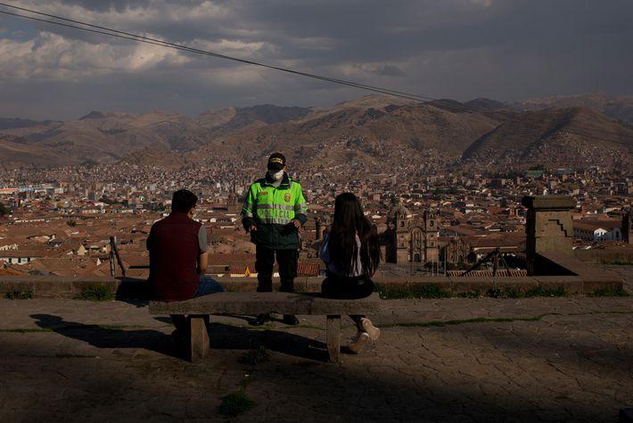 En el otoño de 2020, un policía pide a los lugareños que mantengan la distancia social ...