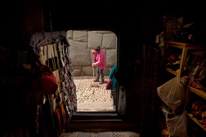 Maria Santos Quispe barre los adoquines en la entrada de su tienda, sobre la calle Hatunrumiyoc ...