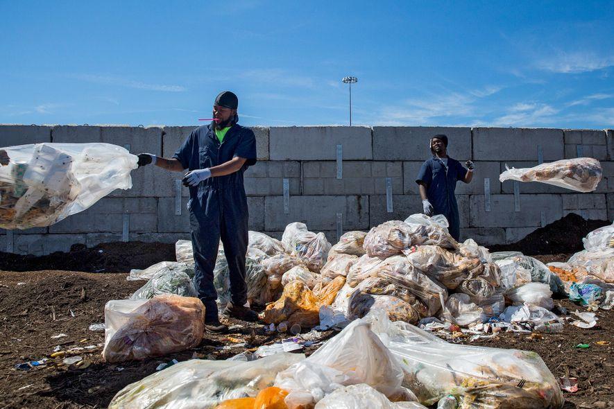 Los trabajadores clasifican las bolsas de residuos de los comedores de las escuelas de la ciudad ...