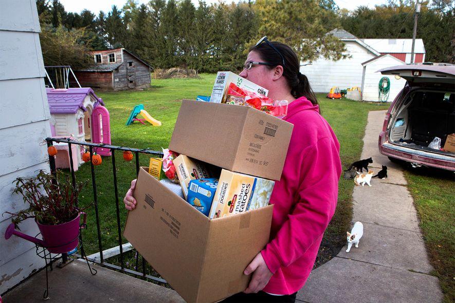 Christina Dreier trae a casa provisiones de una organización benéfica en el condado de Mitchell, Iowa. ...