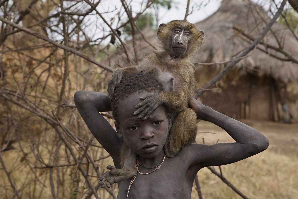 Un niño etíope y su babuino mascota se hacen compañía en la aldea Suri de Tulgit.