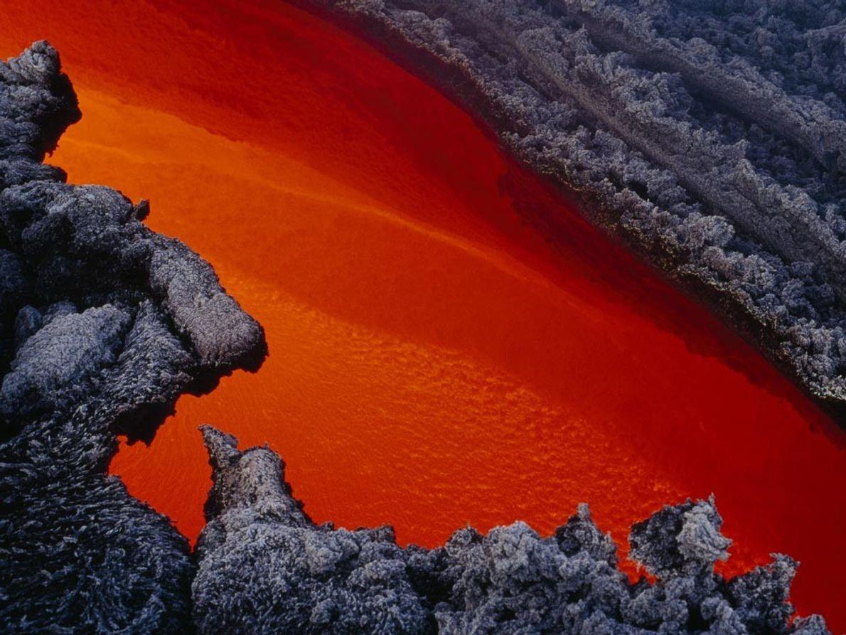 Un río de lava fundida fluye a través de un canal de lava endurecida tras una ...