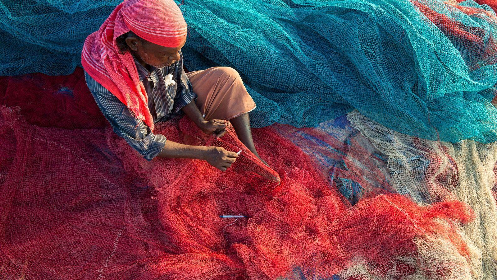 Un pescador en Kerala, India, arregla sus redes en la playa. La contaminación por plástico puede ...