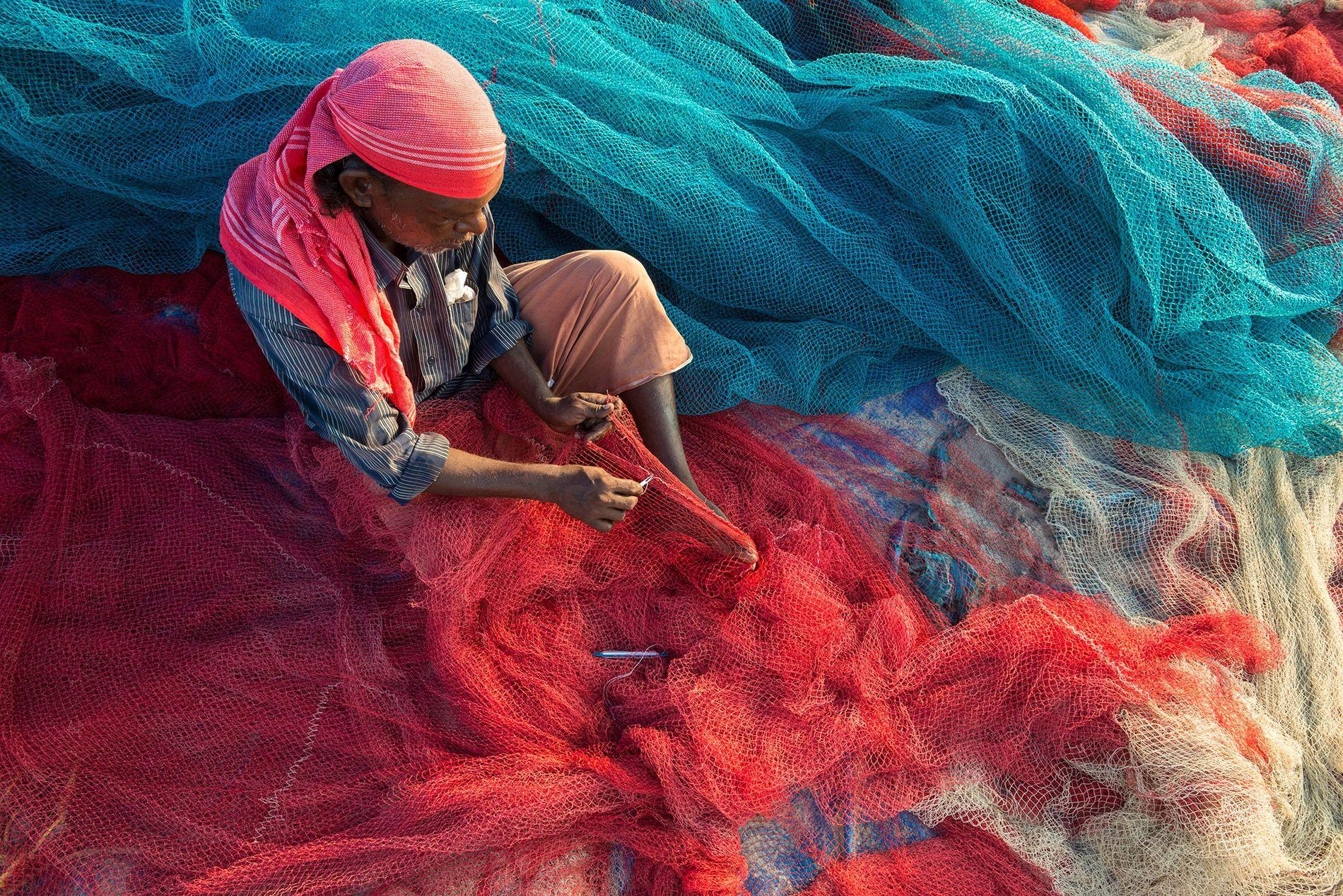 Un pescador en Kerala, India, arregla sus redes en la playa. La contaminación por plástico puede dañar y obstruir redes, pero ahora los pescadores le están haciendo frente.