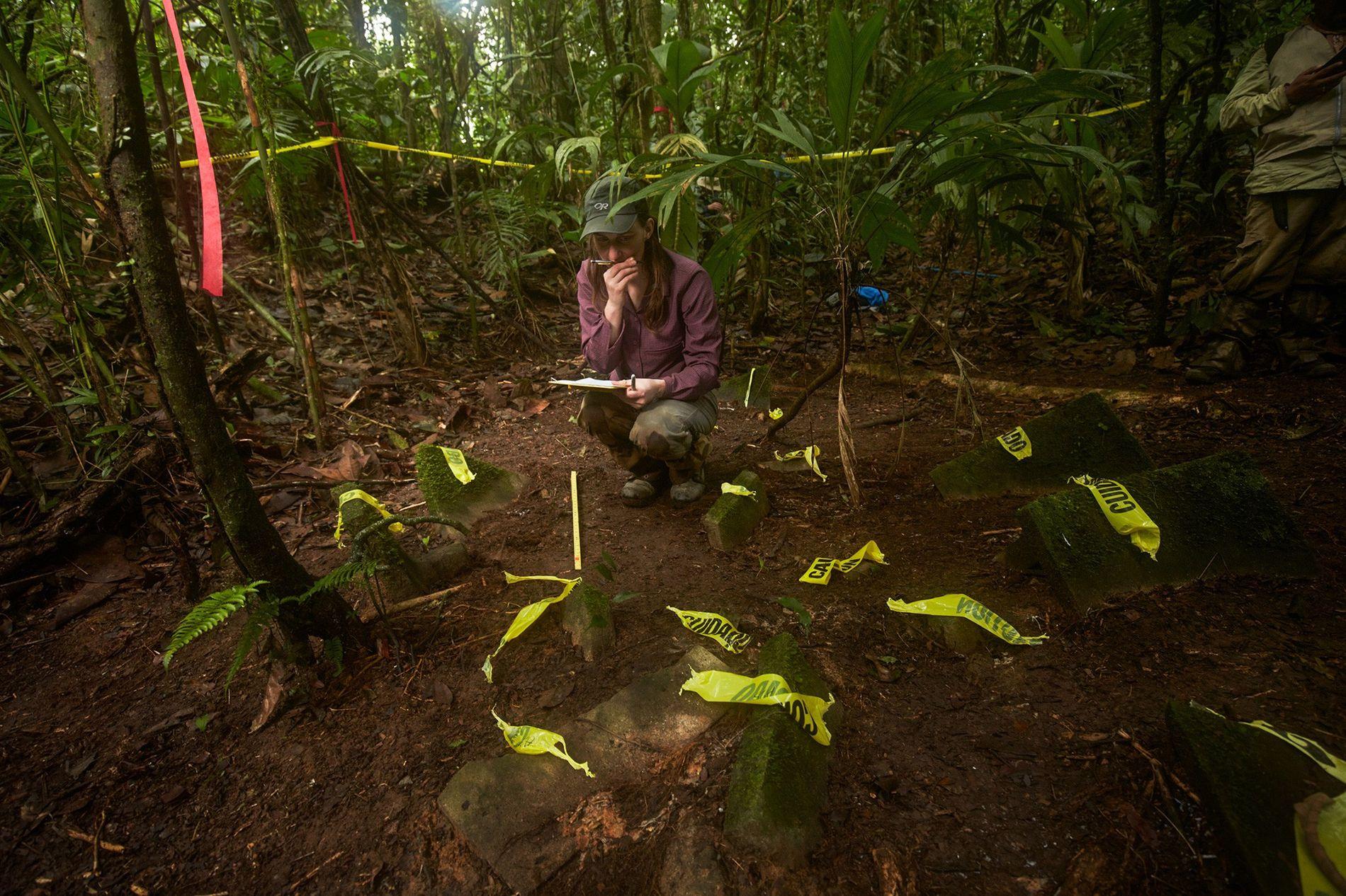 Anna Cohen, una estudiante graduada de antropología de la Universidad de Washington, documenta un alijo de más de 50 artefactos descubiertos en la selva. Según el protocolo científico, no retiraron objetos del sitio. Los científicos esperan poder montar una expedición pronto para documentar y excavar más el sitio antes de que los saqueadores encuentren el lugar.