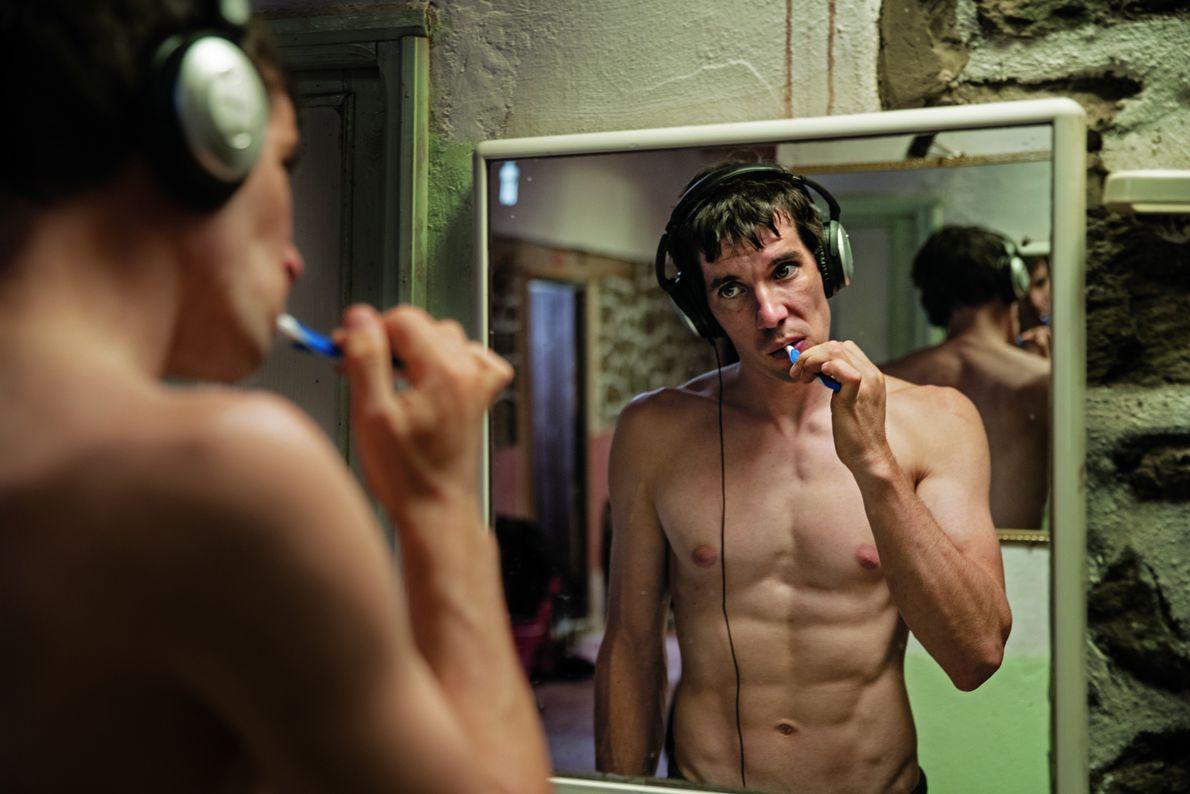 Honnold, de 33 años, escucha música mientras se cepilla los dientes. Se prepara para un día ...