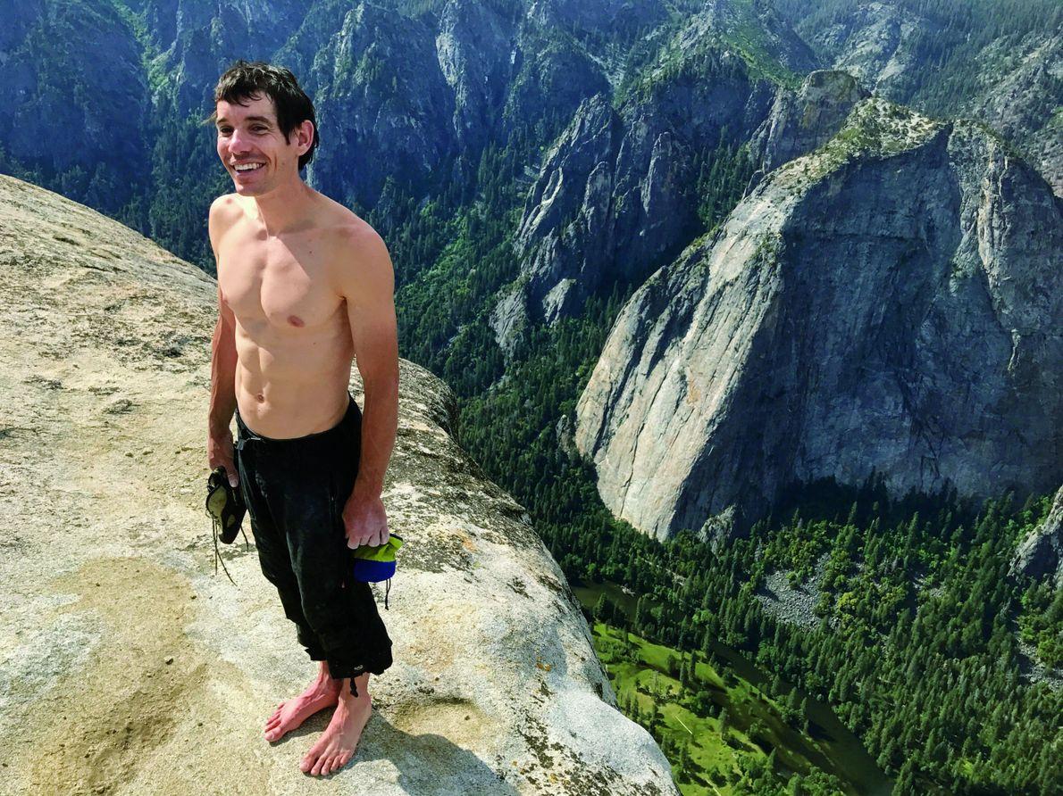 Sosteniendo todo su equipo de escalada (sus zapatos y su bolsa de tiza), Honnold se para …