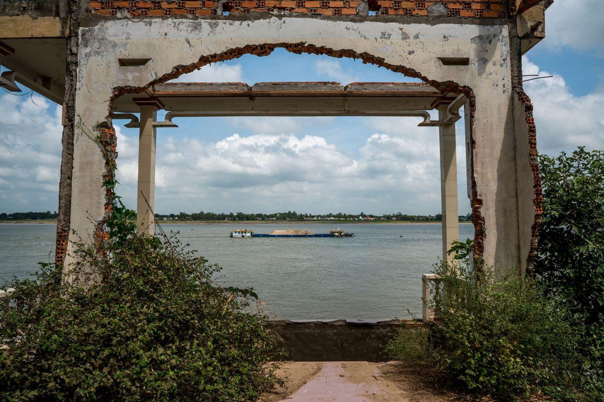 Una barcaza cargada con arena recién dragada pasa por una casa abandonada en el río Tien, ...