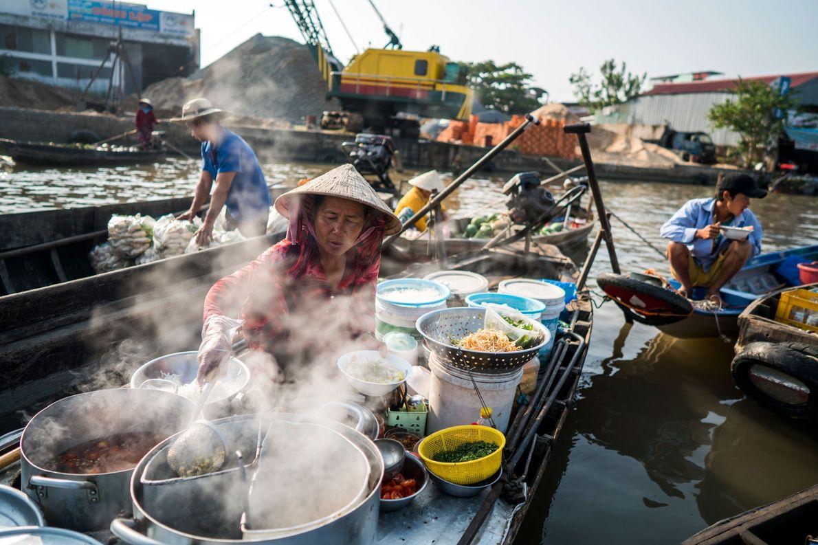 Nguyen Thi Hoang Lien, un vendedor de fideos, sirve tazones de fuente de desayuno a otros ...