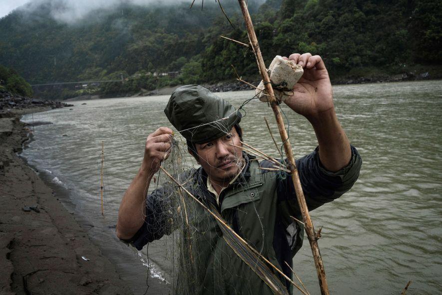 Li Xin Zheng, un agricultor de 36años, prepara una red para atrapar peces en Chala. Muchos ...