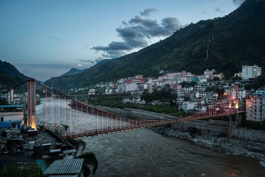 Un puente colgante sobre el río Nu se ilumina en Fugong, una de las ciudades más ...