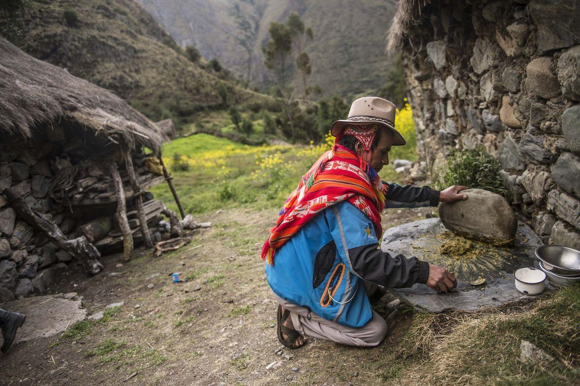 Mario, un agricultor local del Valle Sagrado de Perú, machuca ingredientes locales con una piedra gigante, ...