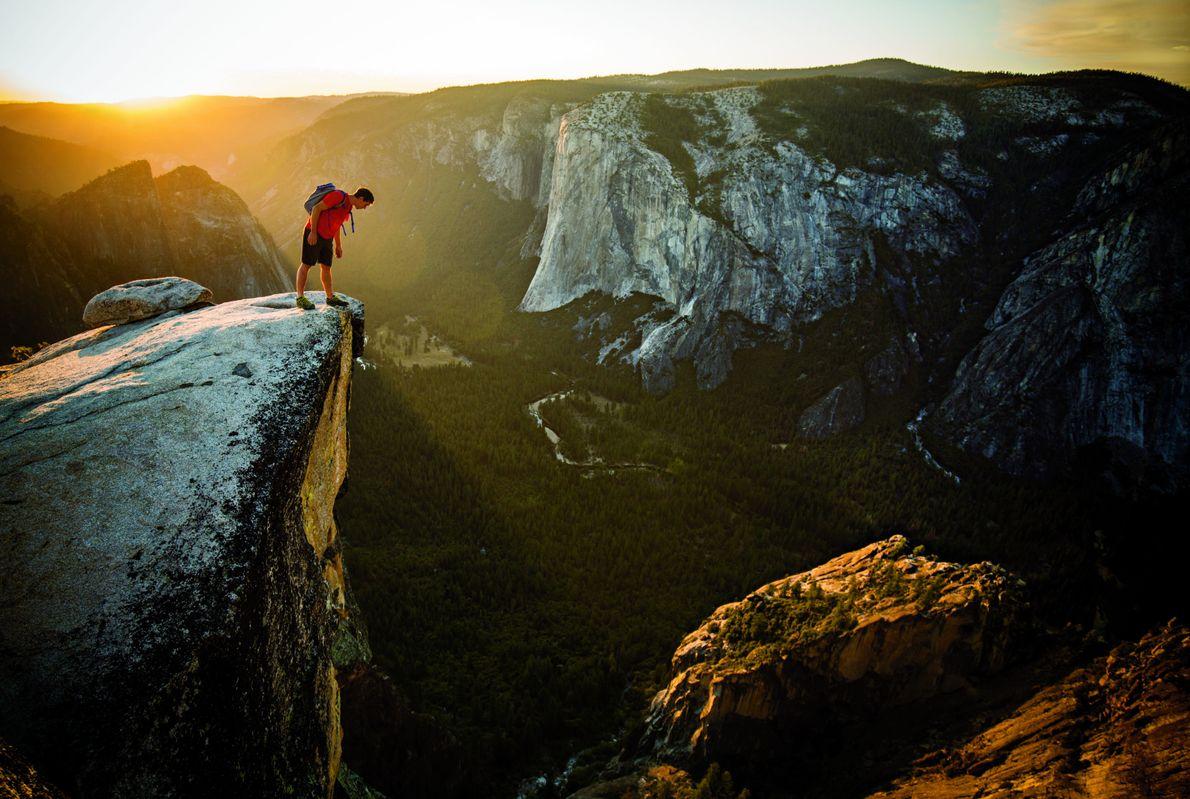 Honnold mira por encima del borde de Taft Point, a través del valle de Yosemite desde ...